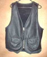"The black motorcycle vest has a large brass (YKK #10) zipper and two patch pockts with flaps. It also has a 3"" back/bottom draft flap extension. Clicking on the link will bring you to a page with a rear view, etc."