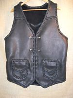"This braided motorcycle vest has slanted front yokes, a pointed back yoke, patch hip pockets with flaps, two sets of 'trick braid' leather snap closures, and a curved 3"" back/bottom draft flap. This vest also has four more pockets that you can't see in this picture. Clicking on the link will bring you to (7 more) pictures of it's different features."