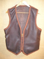 This two tone brown moccasin cowhide leather vest has the extended back/bottom draft flap and a (YKK #10) zipper closure. It also has inside panel pockets. Also pictured on the page linked to it is a zipper extension that I made for it.