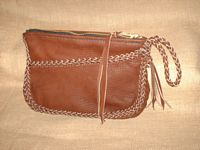 "This picture is of a leather clutch purse constructed with 1/4"" laces cut from the 4 oz. moccasin cowhide that it is made with. It is braided around its seam, across the front pocket, and its strap with tassels. The large zippered closure is hand sewn with 5 ply nylon thread and has a long strap fastened to its tab/slider."