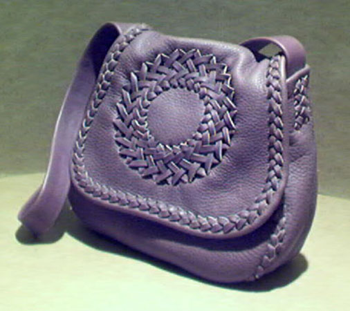 "This handmade purse is made with 4 oz. moccasin cowhide leather. It is completely constructed with braiding using 1/4"" wide laces out of that same leather. It has a long wide strap, a circle applique on the front, and a full width pocket on the inside/back of it. Leather, made in the USA, is the only material used for this purse."