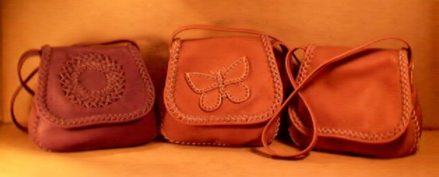 "This picture shows the usual three ways that I build these braided leather handbags. One has a braided circle on the flap, another has a butterfly braided on the flap, and the third one has a plain flap. All of these bags' seams, flap edges, and appliques are braided using 1/4"" wide laces of the same leather the bag is made."