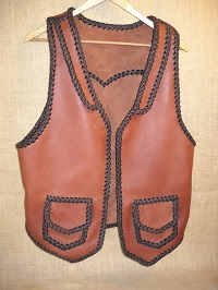 This two tone leather vest was built with moccasin cowhide. It has front lapels, a back pointed yoke, and two patch hip pockets with flaps.