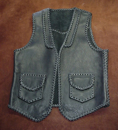 This leather vest has all of it's seams and edges braided. It also has braided lapels on the front, a pointed yoke on the back, and two patch hip pockets with flaps. It also has matching hip pockets on the inside of the front (without flaps).