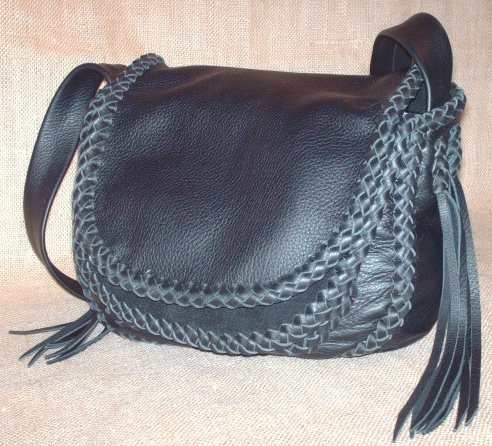 "This custom and handmade leather purse is constructed with 4 oz. moccasin cowhide. All of the pieces of the purse are braided together with 1/4"" wide laces cut from the same soft strong leather the bag is made with - all of the seams are joined with an applique braid, it's double flaps are braided all around their edges, the front pocket is attached with braiding, the strap has an applique braid down the center/length of it ...and the strap is attached with a braid that long tassels hang from."
