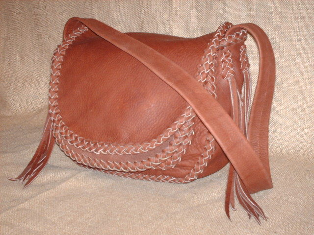These four pictures show a custom, handmade shoulder leather bag made with Rust colored moccasin cowhide leather - it has no hardware, no lining, nor is any thread used in this braided construction. The strap of this one doesn't have braiding down the length of it.