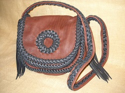 "This handmade custom leather purse was made with Mahogany pieces braided together with dark Brown laces. Like a lot of the purses and handbags that I make, it has no hardware, lining, or thread. Completely braided with 1/4"" wide lacing are the seams, the edges of the flaps, and down the center/length of the strap. There are long tassels hanging from the strap attachments. It has a circle applique braided on the flap. This purse also has two pockets - one under the flap/s and another full width pocket on the inside/back."