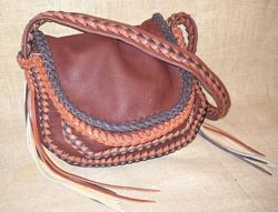 This leather purse is made with four colors. The pieces of the bag are all Mahogany. The color of the leather around its top flap and one of the colors used on the two-tone seams is dark Brown. The color Rust is used around the under flap and is the other color used on the seams. This one has a braided strap with the same two-tone braid down the length of it. The lightest color, Walnut, is used for some of the side tassels.