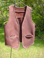 This brown moccasin cowhide leather vest has no front lapels or yokes. It does have a straight back yoke and slit hip pockets (without flaps).