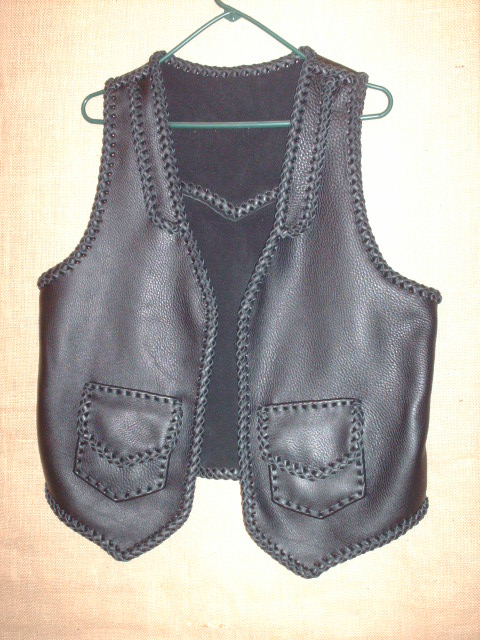 This custom black leather vest was made with moccasin cowhide leather. It's features include lapels on the front, a back pointed yoke, and two patch hip pockets with flaps.