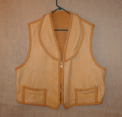 This custom leather vest was fashioned after a vest that the buyer sent me. He also sent me the Elk skin to make it with. I decided to use my moccasin cowhide laces as that would make for a stronger vest. It has a shawl collar, two low hip pockets with two more matching hip pockets on the inside (four pockets in total).