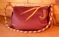 This small bag has a Mahogany colored leather body and a zipper closure. The braided seams and strap were done with Mahogany and Chestnut colored leather ...as is the 'J' applique on the side of it.