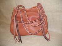 This Rust colored leather tote has two tone braiding (Rust and Mahogany). It has the two front pockets and the back inside pocket. It also has eight strand round braided straps with eight long tassels hanging from each end of them.
