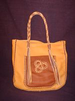 This front picture of this two tone tote shows the front pocket with the applique. It also shows the braided straps and the very long tassels that hang from each end of them.