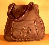 This large Black tote has a more elaborate braid on the bags seams. It also has a circle applique on the large front pocket and another full width back/inside pocket.