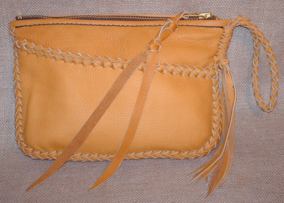 "This leather clutch purse is completely made with a braided construction ...such as its main seam, the top of the pocket, and the wrist strap with tassels hanging from it. It has a large brass zipper closure with a leather strap fastened to the tab/slide. It's about 9"" wide by 6"" high."