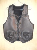 "This black moccasin cowhide leather vest has slanted front yokes, a pointed back yoke, two patch hip pockets (without flaps), and four sets of 'trick braided' leather snaps for closures. It also has the draft flap that so many of my customers have taken a liking to. This draft flap is a 3"" extension of the back that can better be seen on the page that this picture is linked to."