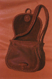 In this picture the purse is lying on it's back with the flap open, you can see the the two compartments that are under the flap. You can see the braided seams, flap edges, strap, and the roll button closure that it has.