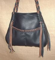 This Black tote with two tone (Black and Mahogany) braiding has long should straps that have long fringe hanging from the ends of them. The straps are also fastened in a different location than the other straps are. It does have the two front pockets and the inside back pocket that the others have.