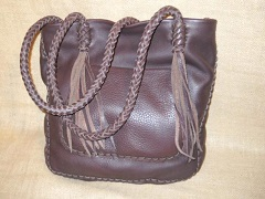 This tote is very much a one of a kind. It was built with full grain, dark Brown, moccasin cowhide leather. It has an outside pocket on the front and a full width pocket on the inside/back. The straps are eight strand round braided with eight strands of long tassels hanging from each end.