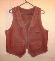 This brown moccasin cowhide leather vest has both lapels and slanted yokes on the front of it - that's what the buyer wanted. It also has a pointed back yoke, a single slit breast pocket (credit dard size), and two patch hip pockets (with matching inside pockets). The picture is linked to a page of more views of the vest and its features.