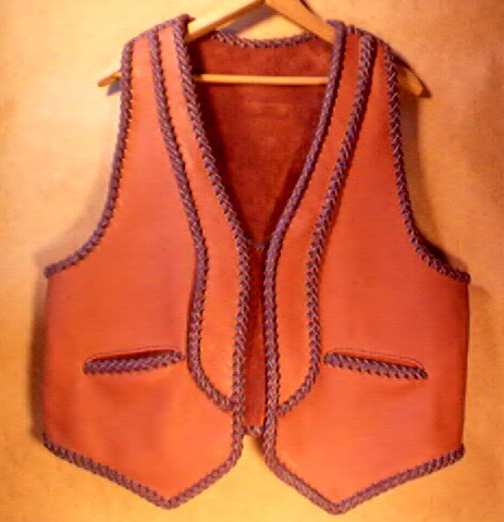 This two tone moccasin cowhide leather vest has rather uniques lapels and back yoke on it - the back yoke can be better seen by going to the page the picture is linked to. It also has the two slanted slit pockets.