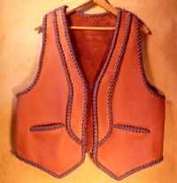 This two tone moccasin cowhide leather vest has rather uniques lapels and back yoke on it - the back yoke can be better seen by going to the page the picture is linked to. It also has the two slanted slit pockets