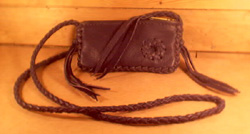 "This small Black bag is about 7"" long by 4"" high and has a zipper across the top of it. It has a 4 strand round braided strap that has long tassels hanging from the ends of it. It has a small circle applique braided to the side of it."
