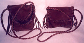 "These two small leather purses are completely braided. One is about 7"" high by 4"" wide ...and the other is about 7"" wide by 4"" high. Both have 4 strand braided shoulder straps with tassels on their ends."