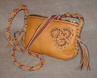 "This small two-tone bag is about 9"" long by 6"" high. It has a zipper across the top of it. The long 8 strand braided shoulder strap has tassels hanging from the ends of it. There is (what I call) a 'tri-loop' applique braided to the side of it."