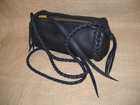 "This Black barrel bag is about 9"" long with a 5"" diameter and has zipper across the top of it. It has a 4 strand round braided shoulder strap with long tassels hanging from the ends of it. It also has a very long strap of leather tied to the zipper tab/slide."