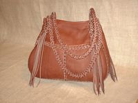 This Mahogany colored tote has the same front pockets and back inside pocket that most of the others have. The braided strap it has have long tassels hanging from them.