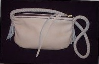 The bag is entirely made with Cream leather. It has a pretty short strap that has quite short tassels.