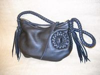 This Black bag has a braided circle applique on the side of it. 8 tassels hang from each end of the 8 lace braided strap. A leather lace is also attached to the zipper slide.