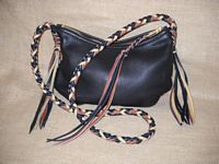 This body of this bag is made with my dark Brown leather. It's seam is of two colors ...that dark Brown and Mahogany. The strap is of three colors - dark Brown, Mahogany, and Cream - the tassels are an extension of the strap.     The leather on the zipper slide is different than I do on most slides ...it's braided with the same two colors as the seams - dark Brown and Mahogany.