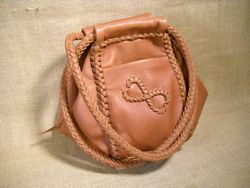 A unique leather handbag with an 'infinity hearts' applique on one of the pockets.