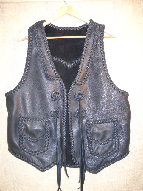 This custom, handmade moccasin cowhide leather vest was made in the USA using leather that was tanned in the USA. It features front lapels, a pointed back yoke, two patch hip pockets with flaps, and some straps that hang from some braided leather conchoes that I fashioned.